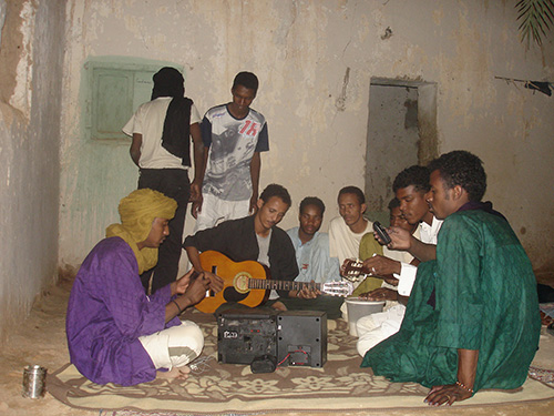 Young ishumar from Niger living in Libya sit every night together in order to play guitar, listen to Tuareg music tapes, and discuss border crossings, and dream of the future. (Photo: Ines Kohl 2007).