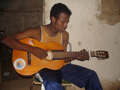 "Young ishumar tried to escape their vicious circle of missing chances and perspectives by learning guitar, and copy the well known ""heroes"" of Tuareg music, such as Tinariwen, or Abdallah Oumbadougou. (Photo: Ines Kohl, 2008)."